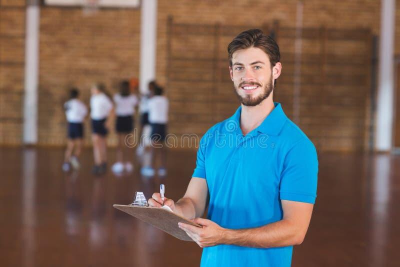 Portrait de l'écriture de professeur de sports sur le presse-papiers image stock