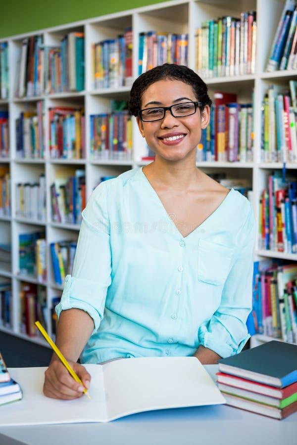 Portrait de l'écriture heureuse de femme sur le carnet dans la bibliothèque images stock