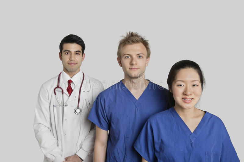Portrait de l'équipe médicale ethnique multi sûre se tenant au-dessus du fond gris photographie stock