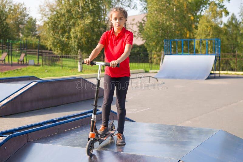 Portrait de l'équitation mignonne de petite fille sur un scooter de cick images libres de droits