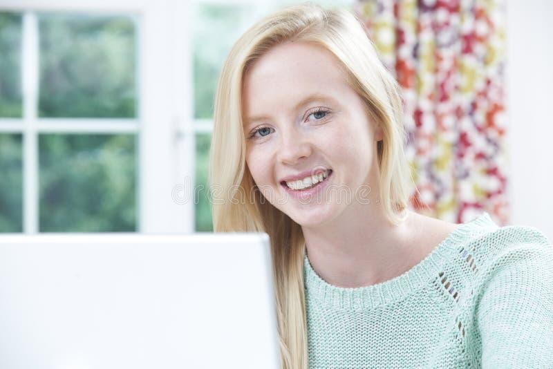 Portrait de l'adolescente à l'aide de l'ordinateur à la maison photographie stock