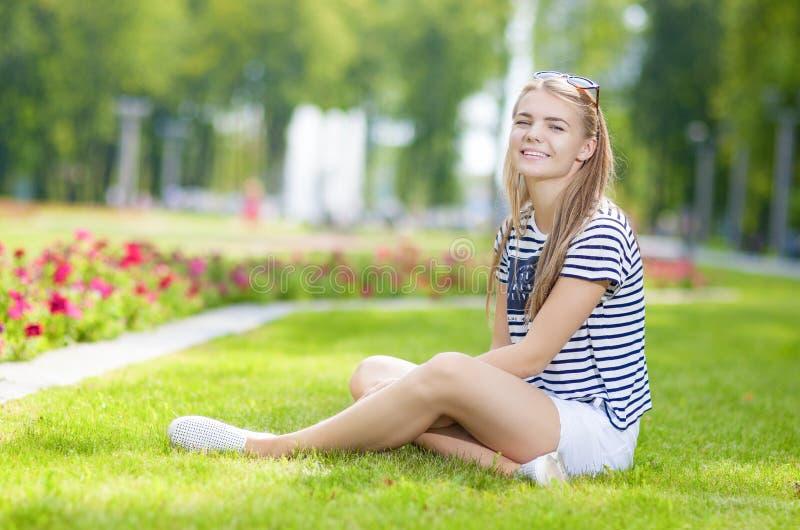 Portrait de l'adolescente caucasienne de sourire heureuse posant sur l'herbe en parc fleuri vert d'été images stock