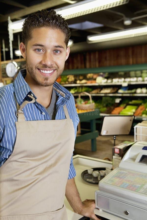 Portrait de l'employé bel de magasin tenant la caisse enregistreuse proche dans le supermarché photographie stock libre de droits