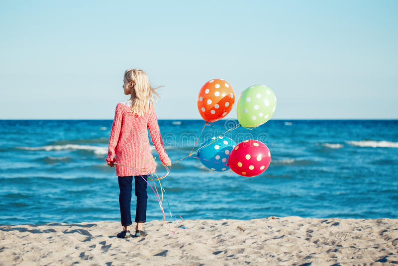 Portrait de l'enfant caucasien blanc d'enfant d'adolescent songeur avec le groupe coloré de ballons, se tenant sur la plage sur l photographie stock