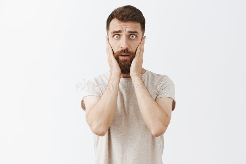 Portrait de l'entrepreneur masculin élégant bel commençant la panique regarder concerné et inquiété tenant des mains sur le visag photographie stock
