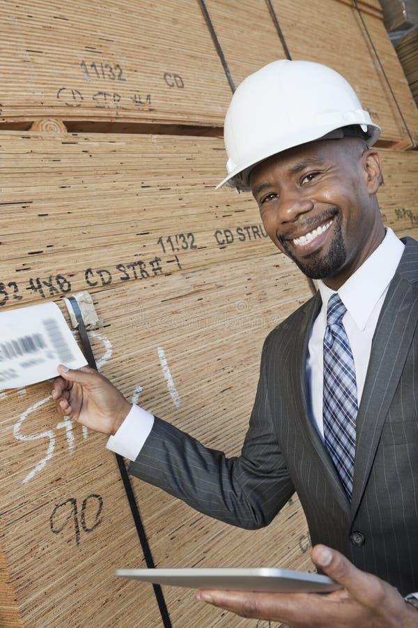 Portrait de l'entrepreneur masculin d'Afro-américain heureux à l'aide du PC de comprimé tout en inspectant les planches en bois photos stock