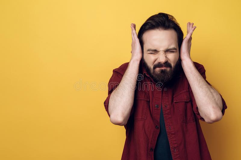 Portrait de l'homme attirant intéressé couvrant des oreilles image stock