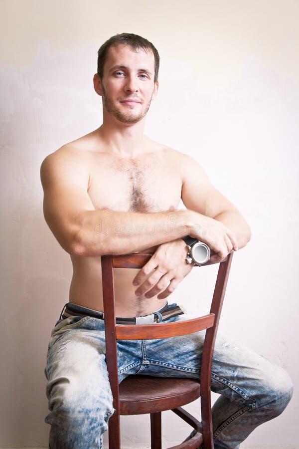 Portrait de l'homme attirant réfléchi s'asseyant sur une chaise photographie stock