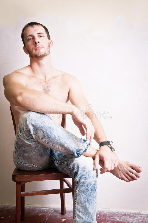 Portrait de l'homme attirant réfléchi s'asseyant sur une chaise photo stock