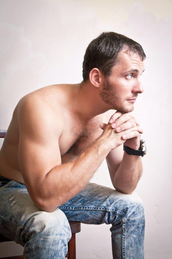 Portrait de l'homme attirant réfléchi s'asseyant sur une chaise photographie stock libre de droits