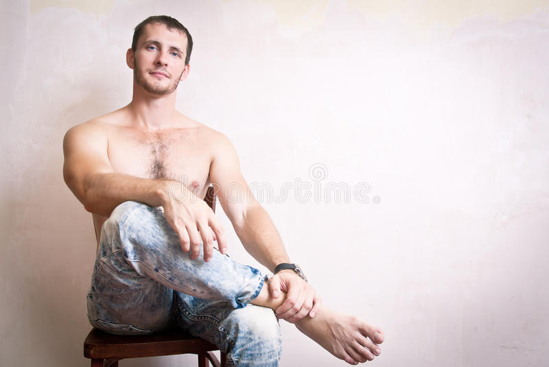 Portrait de l'homme attirant réfléchi s'asseyant sur une chaise images stock