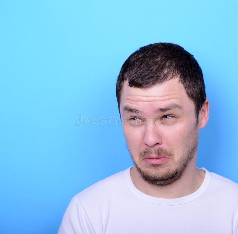Portrait de l'homme avec le geste dusgusted sur le fond bleu images libres de droits