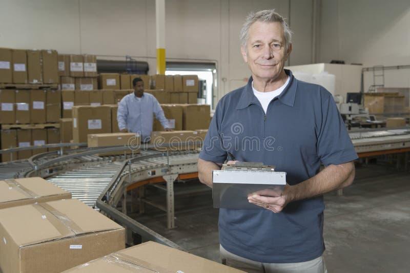 Portrait de l'homme avec le travailleur derrière à l'entrepôt photos libres de droits