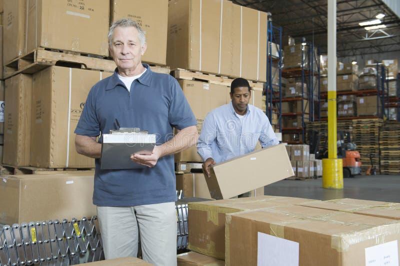 Portrait de l'homme avec le travailleur derrière à l'entrepôt photo stock
