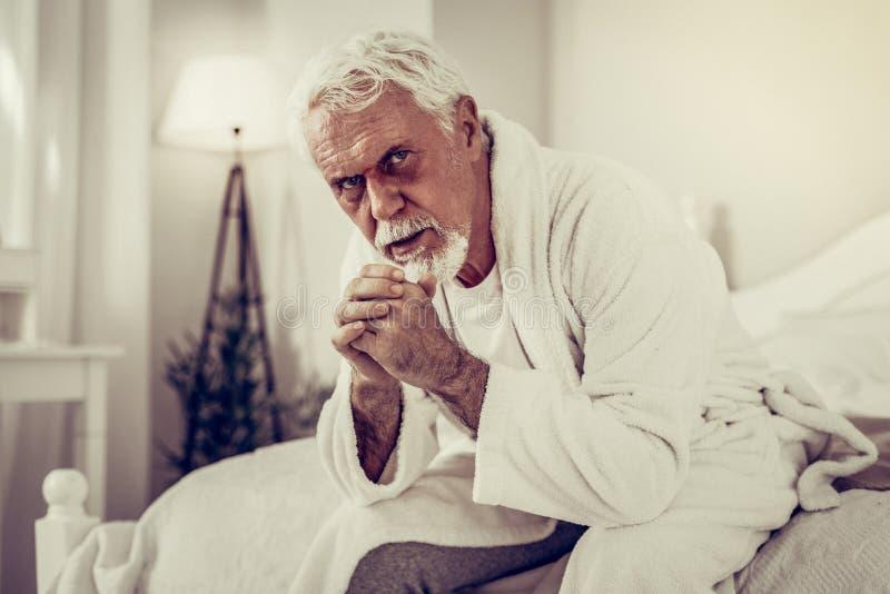 Portrait de l'homme avec l'oeil au beurre noir se reposant sur un lit image libre de droits