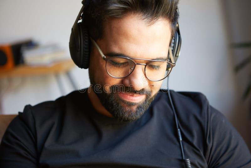 Portrait de l'homme barbu bel dans des écouteurs écoutant la musique à la maison Concept de temps de détente et de repos brouillé image stock