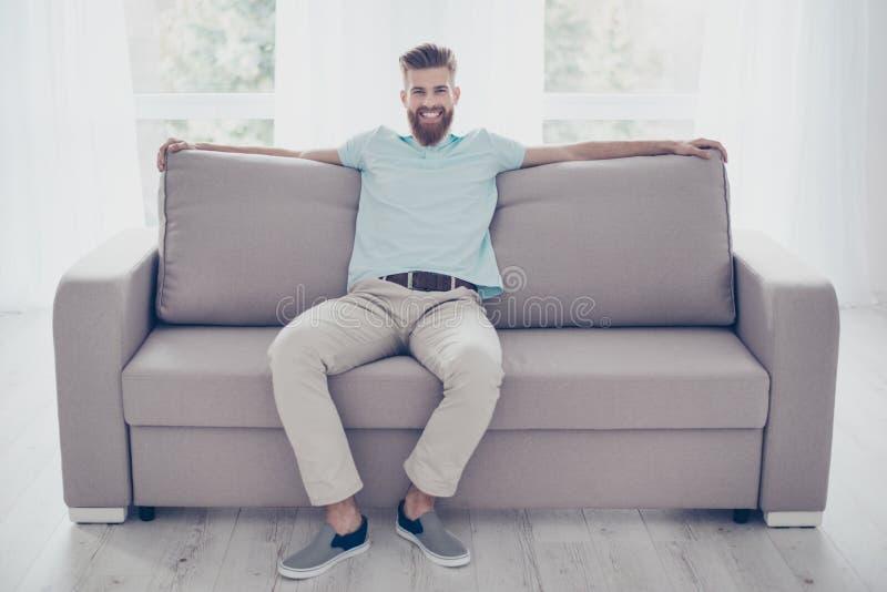 Portrait de l'homme barbu bel de sourire décontracté se reposant sur confortable image stock