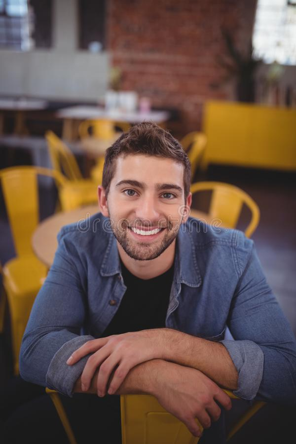 Portrait de l'homme bel de sourire s'asseyant sur la chaise image stock