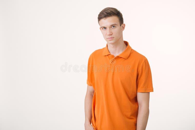 Portrait de l'homme châtain bel utilisant la chemise orange semblant la position paisible au-dessus du fond blanc photo libre de droits