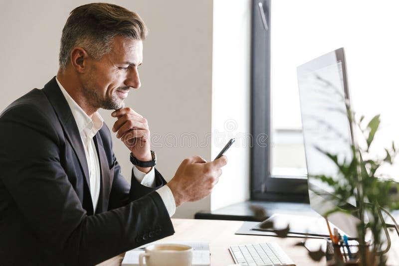 Portrait de l'homme d'affaires attirant à l'aide du téléphone portable tout en travaillant sur l'ordinateur dans le bureau photos libres de droits