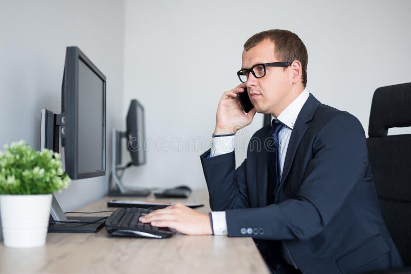 Portrait de l'homme d'affaires bel ? l'aide de l'ordinateur et parlant par le t?l?phone dans le bureau photo libre de droits