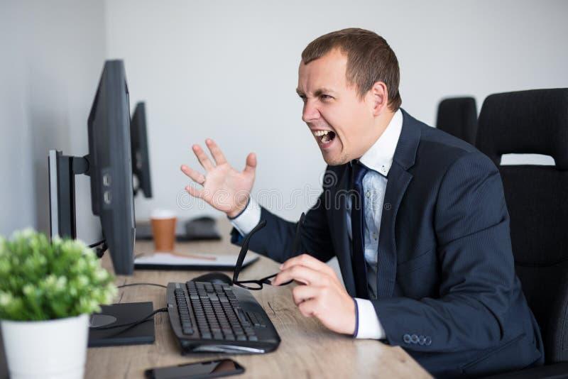 Portrait de l'homme d'affaires soumis ? une contrainte criant sur son ordinateur dans le bureau moderne photo libre de droits