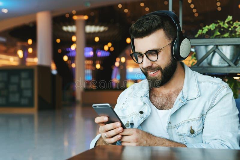 Portrait de l'homme dans des écouteurs se reposant en café, écoutant la musique, vidéo de observation, webinar sur le smartphone, image libre de droits