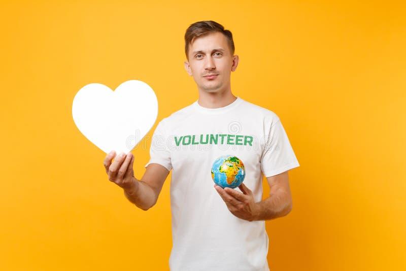 Portrait de l'homme dans le T-shirt blanc avec le titre écrit de vert d'inscription coeur volontaire de blanc de prise, globe du  photographie stock libre de droits