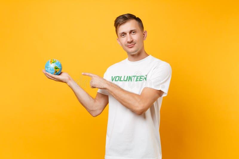 Portrait de l'homme dans le T-shirt blanc avec le titre écrit de vert d'inscription participation volontaire en globe du monde de image libre de droits