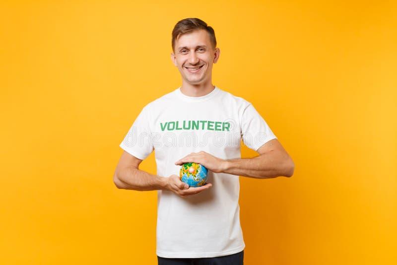 Portrait de l'homme dans le T-shirt blanc avec le titre écrit de vert d'inscription participation volontaire en globe du monde de photographie stock