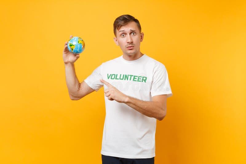 Portrait de l'homme dans le T-shirt blanc avec le titre écrit de vert d'inscription participation volontaire en globe du monde de images stock