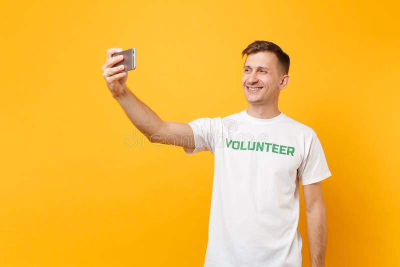 Portrait de l'homme dans le volontaire de titre de vert d'inscription écrit par T-shirt blanc prenant le selfie tiré au téléphone photos stock