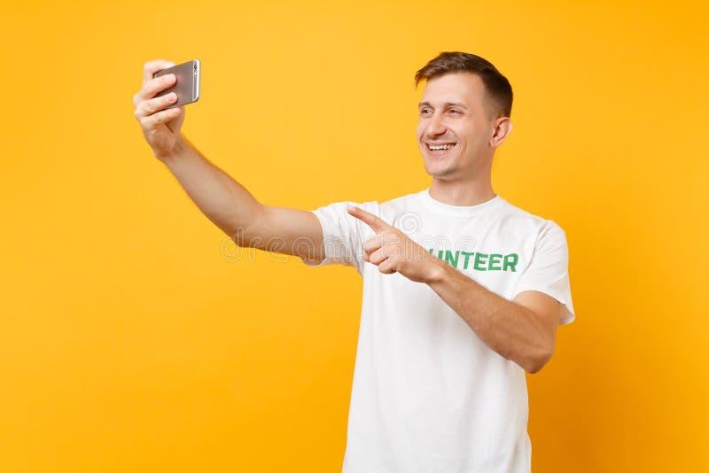Portrait de l'homme dans le volontaire de titre de vert d'inscription écrit par T-shirt blanc prenant le selfie tiré au téléphone photo libre de droits