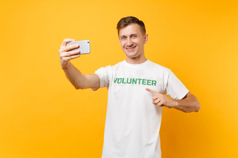 Portrait de l'homme dans le volontaire de titre de vert d'inscription écrit par T-shirt blanc prenant le selfie tiré au téléphone photos libres de droits