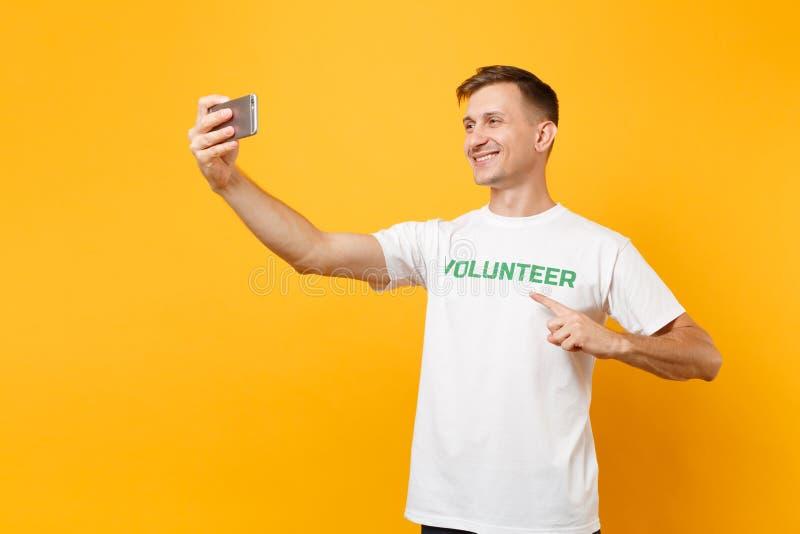 Portrait de l'homme dans le volontaire de titre de vert d'inscription écrit par T-shirt blanc prenant le selfie tiré au téléphone images libres de droits