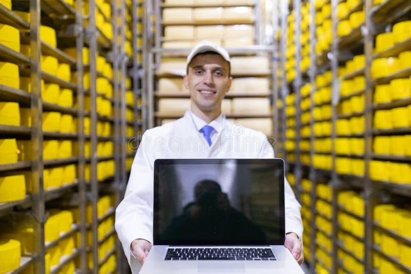 Portrait de l'homme dans une robe longue blanche et d'une position de chapeau dans le d?partement de production de l'usine de lai images stock