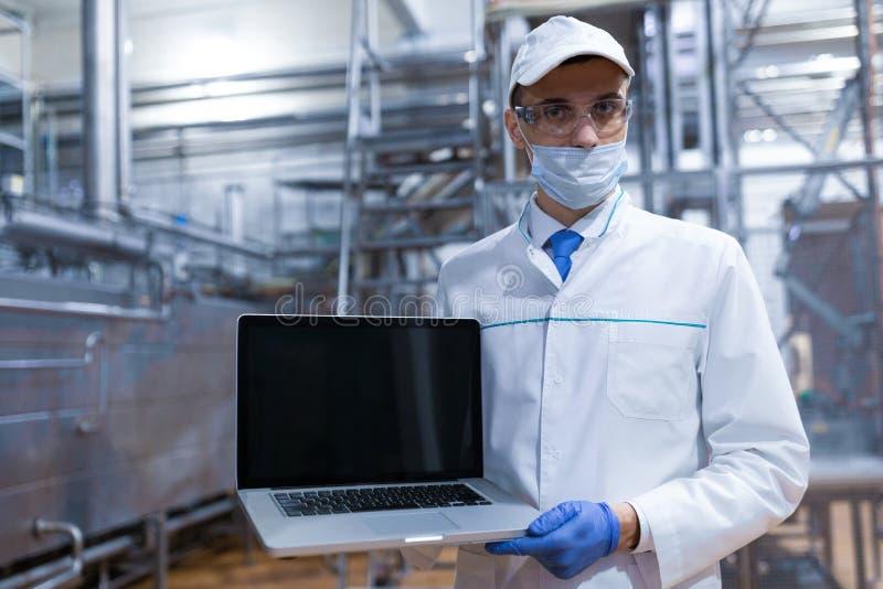 Portrait de l'homme dans une robe longue blanche et d'une position de chapeau dans le d?partement de production de l'usine de lai image stock