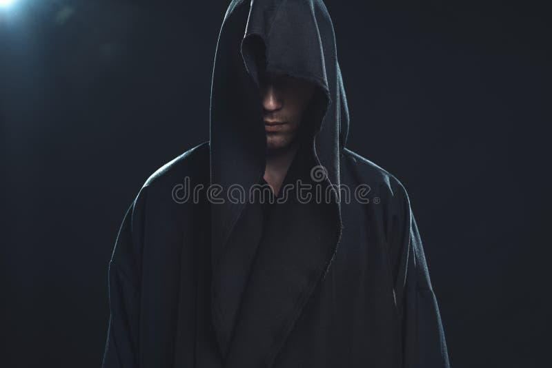 Portrait de l'homme dans une robe longue noire photos stock