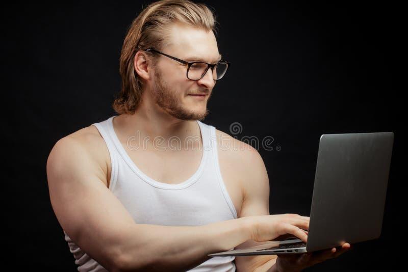 Portrait de l'homme de forme physique à l'aide de l'ordinateur portable image libre de droits