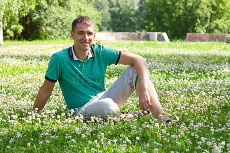 Portrait de l'homme heureux attirant s'asseyant sur l'herbe dehors photo stock