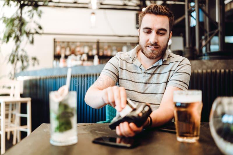 Portrait de l'homme payant au restaurant utilisant la carte de crédit et le terminal sans fil images libres de droits