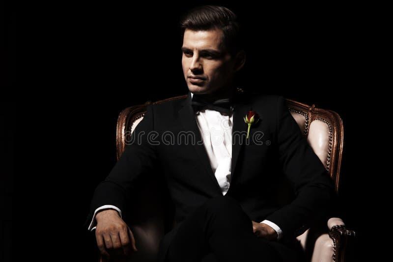 Portrait de l'homme qui s'asseyant sur la chaise image stock