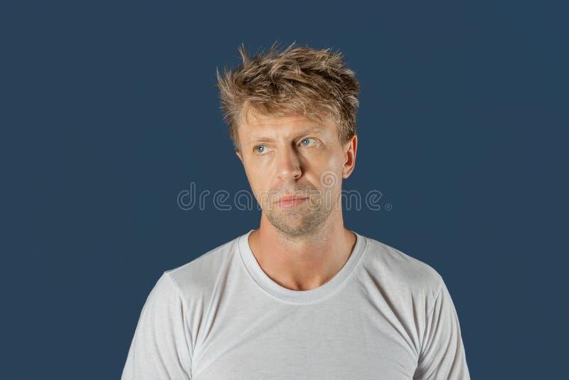 Portrait de l'homme réfléchi triste bel d'isolement au-dessus du fond bleu image libre de droits