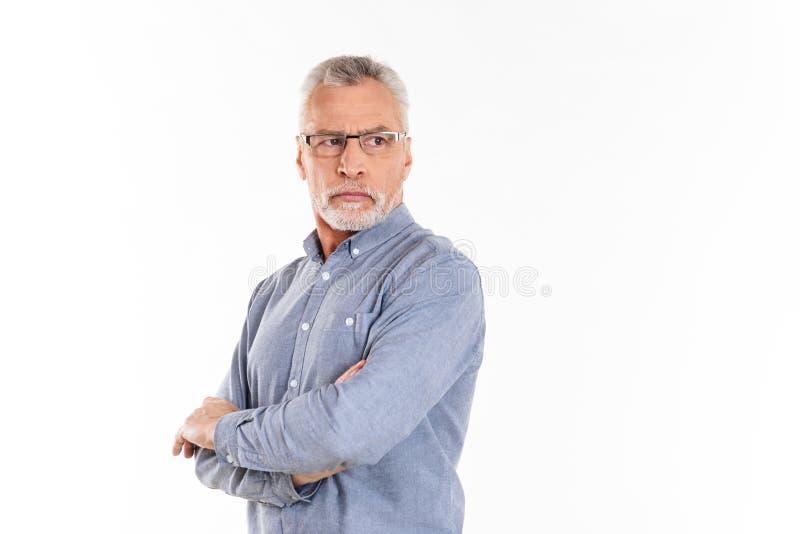 Portrait de l'homme sûr sérieux regardant de côté avec les mains pliées photo stock
