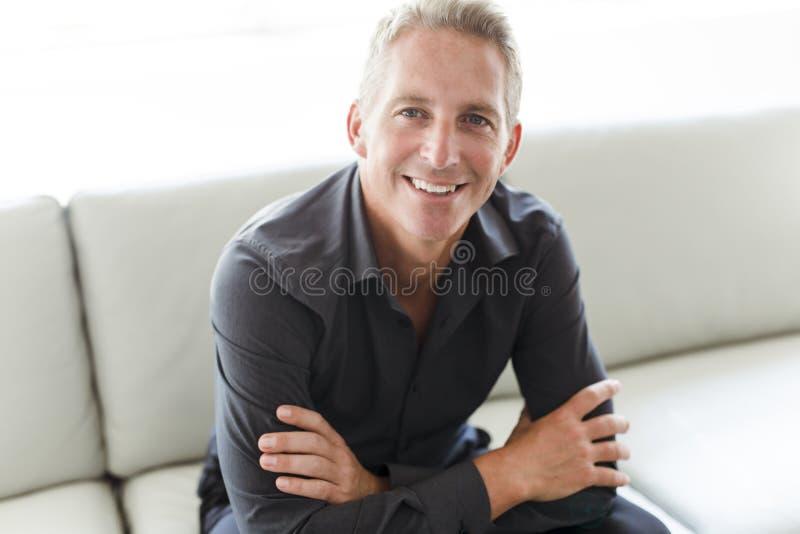 Portrait de l'homme 40s simple s'asseyant dans le sofa images libres de droits