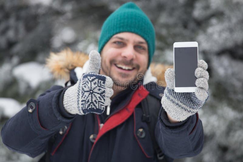 Portrait de l'homme de sourire qui tenant le téléphone et le pouce intelligents  Holi photo stock