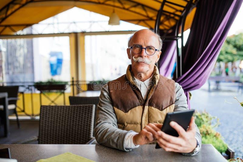 Portrait de l'homme supérieur à l'aide du comprimé numérique en café, foyer sur les mains masculines tenant le dispositif moderne images libres de droits