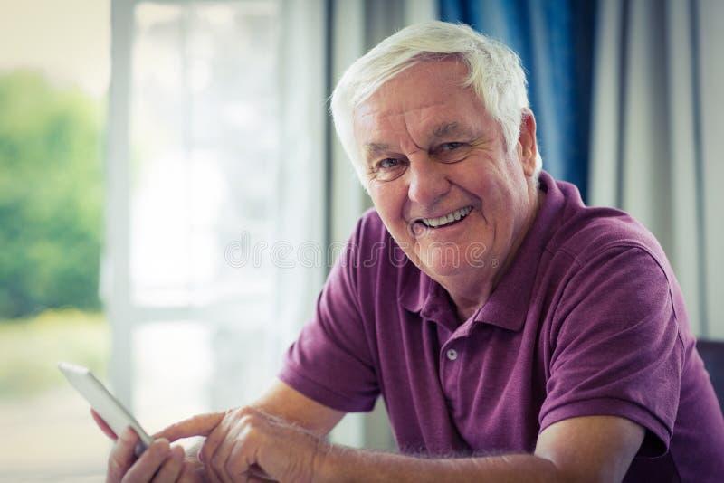 Portrait de l'homme supérieur à l'aide du téléphone portable à la maison images libres de droits