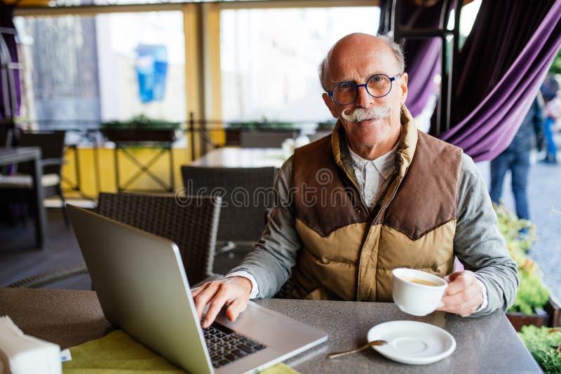 Portrait de l'homme supérieur animé appréciant la tasse de café tout en travaillant avec l'ordinateur portable moderne à la table photo libre de droits