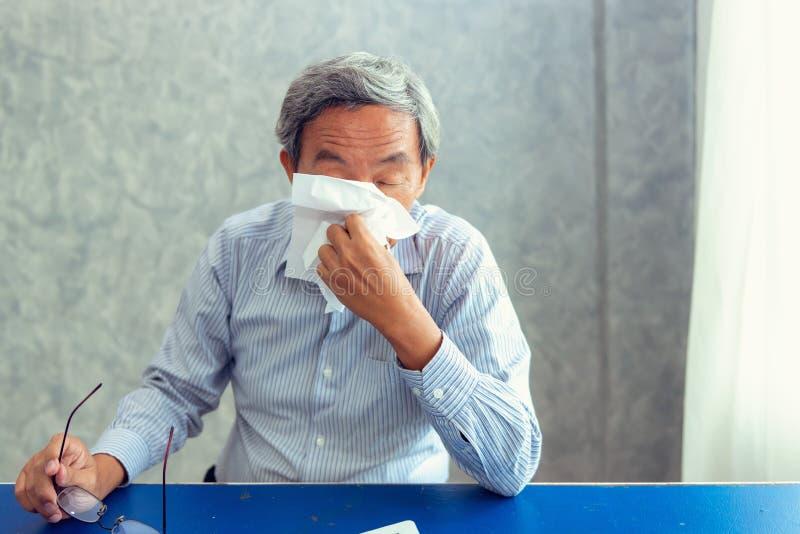 Portrait de l'homme supérieur ayant le malade avec le chiffon de papier soufflant son n images libres de droits